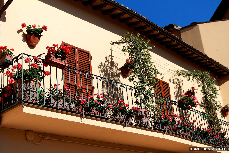 balkon z kwiatami i włoskimi okiennicami